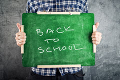 Man holding chalkboard, back to school. Man holding chalkboard with title back to school Stock Photo