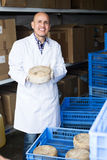 Man holding cheese on factory Stock Photo
