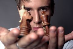 Man holding Chess Pieces. Very handsome young man concentrating on chess Stock Photos