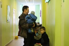 Man holding a child and children stand in line at the hospital receive benefits in a public institution waiting for admission. A man holding a child and children royalty free stock photography