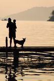 Man holding a child on wooden Pier during sunset with pet, Famil Royalty Free Stock Photos