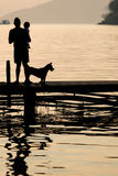 Man holding a child on wooden Pier during sunset with pet, Famil Royalty Free Stock Image