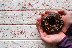 Man holding a chocolate donut Stock Photos