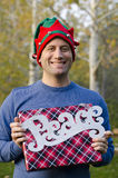 Man holding a Christmas gift and peace sign. Stock Photo