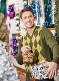 Man Holding Christmas Present And Bauble Basket In Stock Images