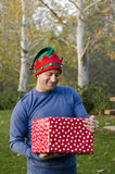 Man holding a Christmas present outside. royalty free stock photography