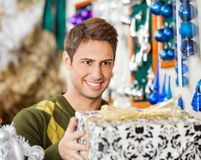 Man Holding Christmas Present In Store Royalty Free Stock Photography