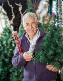 Man Holding At Christmas Tree And Baubles In Store Stock Photos