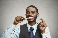 Man holding cigarette and toothbrush Stock Image