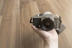 A man holding film camera showing front panel with wooden floor background. A man holding classic film camera showing front panel with wooden floor background royalty free stock image