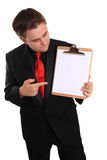 Man holding Clipboard with blank page. Businessman pointing at and holding a clipboard with a blank page on a white background Royalty Free Stock Images