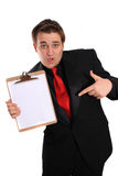 Man holding Clipboard with blank page. Businessman with funny expression pointing at and holding a clipboard with a blank page on a white background Stock Photos