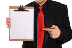 Man holding Clipboard with blank page. Businessman pointing at and holding a clipboard with a blank page on a white background Royalty Free Stock Photos