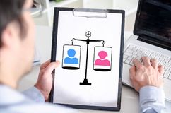 Equality concept on a clipboard. Man holding a clipboard with equality concept royalty free stock image