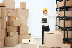 Man holding clipboard and pointing on cartoon box. At warehouse Royalty Free Stock Photos