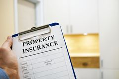 Clipboard with Property insurance. Man holding clipboard with Property insurance Stock Photos