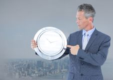 Man holding clock in front of city Stock Photos
