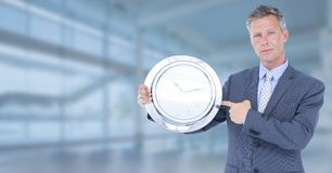 Man holding clock in front of glass hall Royalty Free Stock Image