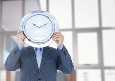 Man holding clock in front of windows Royalty Free Stock Image