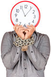 Man holding a clock in place of his face with his hands chained Royalty Free Stock Photos