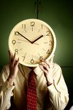 Man holding a clock to his face Stock Images