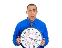 Man holding a clock very stressed, pressured by lack of and running out of time Royalty Free Stock Photo
