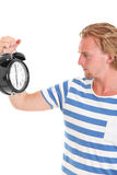 Man holding a clock. Wearing a blue striped shirt. White background Stock Image