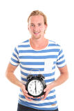 Man holding a clock. Wearing a blue striped shirt. White background Royalty Free Stock Photo