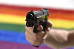 Man holding close up gun with background gay parade flag representing sexual discrimination Stock Photography