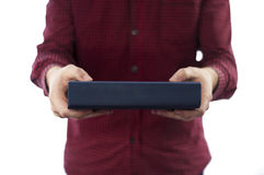Man holding closed book isolated on white. Man holding large closed book with blank spine, isolated on a white background royalty free stock photos