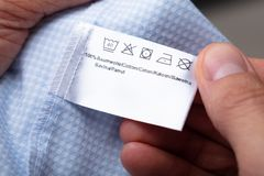 Man Holding Cloth Label Showing Washing Instructions. Close-up Of A Man`s Hand Holding Cloth Label Showing Washing Instructions royalty free stock photography