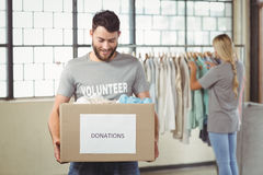 Man holding clothes donation box with woman in background Stock Photos