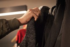 Man holding clothes in a store during shopping. Customer holding clothes in a store during shopping or sales Stock Photos