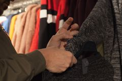 Man holding clothes in a store during shopping. Customer holding clothes in a store during shopping or sales Stock Photo