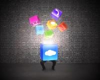Man holding cloud box illuminated app icons with brick wall Royalty Free Stock Photography