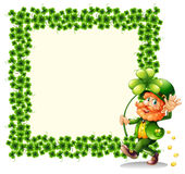 A man holding a clover leaf beside a frame made of leaves Stock Image