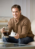Man holding coffee carafe pouring cup of coffee Royalty Free Stock Images