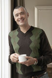 Man Holding Coffee Cup At Doorway Stock Photo