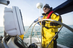 Man Holding Coffee Cup While Standing At Helm Of Sail Boat. Mature man holding coffee cup while standing at helm of sail boat in sea Royalty Free Stock Images