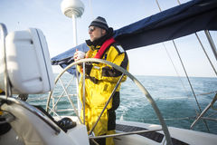 Man Holding Coffee Cup While Standing At Helm Of Yacht. Mature man holding coffee cup while standing at helm of yacht in sea Royalty Free Stock Images