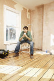 Man Holding Coffee Mug On Step Ladder In Unrenovated Room Royalty Free Stock Photo