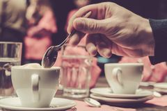 Man holding coffee spoon to stir cappuccino. Male hand holding coffee spoon to stir hot cappuccino in the cafe or restaurant royalty free stock photos