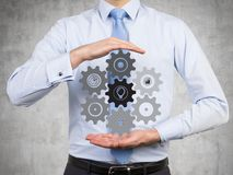 Man holding cogs and gears. Businessman holding drawing cogs and gears Royalty Free Stock Images