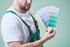 Man holding color swatches. Young man wearing overalls and holding color swatches Royalty Free Stock Photo