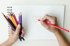 Man holding colored pencils and sketching. Man holding a fistful of colored pencils in one hand while commencing sketching in a sketch book Royalty Free Stock Photo