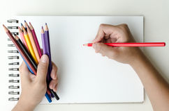Man holding colored pencils and sketching. Man holding a fistful of colored pencils in one hand while commencing sketching in a sketch book to show off his Stock Photos