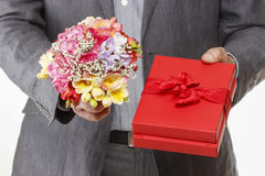 Man holding colorful bouquet of freesia flowers and red box Stock Photo
