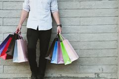 Man holding colorful shopping bag outdoors. shopaholic male stan. Young man holding colorful shopping bag outdoors. shopaholic male standing beside gray wall Stock Photo