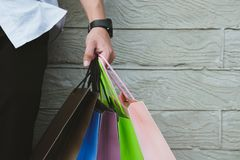Man holding colorful shopping bag outdoors. shopaholic male stan. Young man holding colorful shopping bag outdoors. shopaholic male standing beside gray wall Royalty Free Stock Images