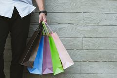 Man holding colorful shopping bag outdoors. shopaholic male stan. Young man holding colorful shopping bag outdoors. shopaholic male standing beside gray wall Stock Photography